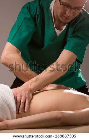 Male physical therapist doing professional back massage - stock photo
