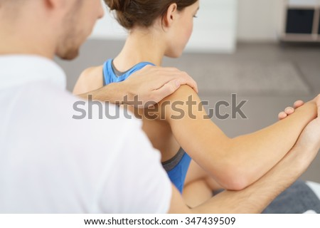 Male Physical Therapist Massaging the Injured Arm and Shoulder of a Young Woman Slowly. - stock photo