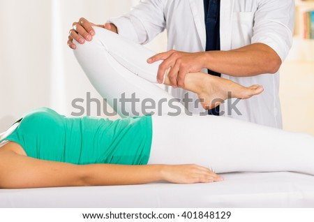Male physio therapist hands working on female patients legs, holding and bending, blurry clinic background