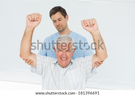 Male physiotherapist assisting senior man to raise hands in the medical office - stock photo