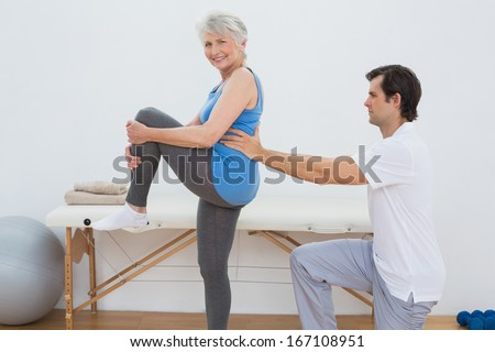 Male physiotherapist examining senior woman's back in the medical office - stock photo