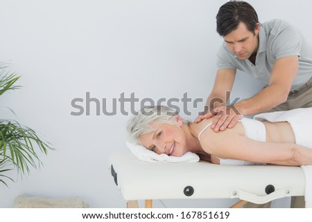 Male physiotherapist massaging a senior woman's back in the medical office - stock photo