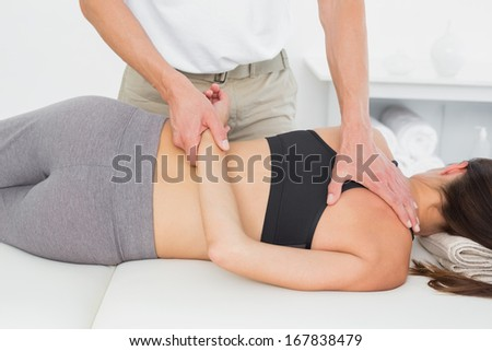 Male physiotherapist massaging woman's body in the medical office - stock photo