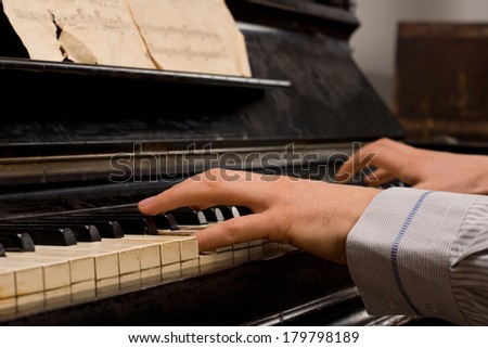 Male pianist practicing sitting at an upright piano playing music from an old score sheet, close up of his hands - stock photo