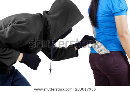 Male pickpocket taking money from pocket of woman while wearing black jacket and mask - stock photo