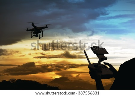 Male pilot controlling drone with remote control - stock photo