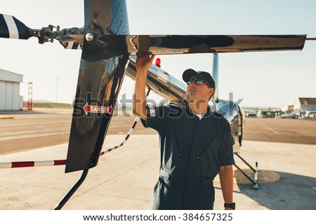Male pilot in uniform examining helicopter tail wing. Pre flight inspection by pilot at the airport. - stock photo