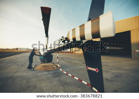 Male pilot inspecting helicopter before take off. Pilot preparing his helicopter for flight - stock photo
