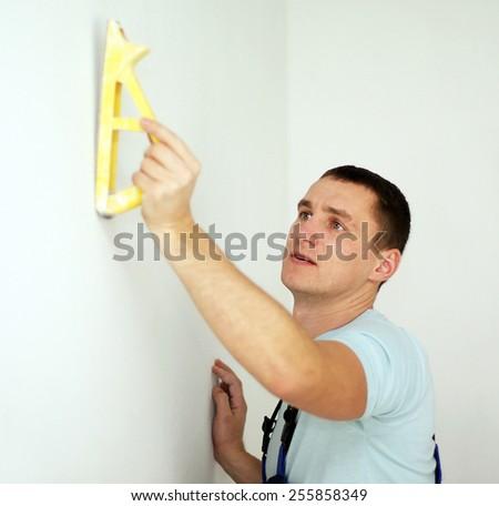 Male plasterer in uniform polishing the wall - stock photo