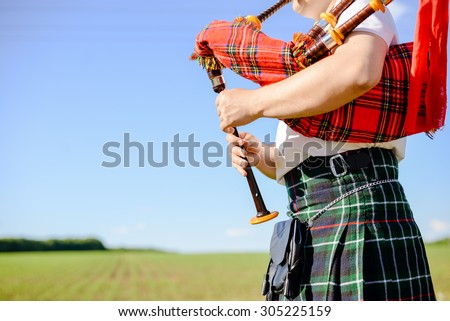 Male playing Scottish traditional pipes on green summer outdoors background, closeup image  - stock photo