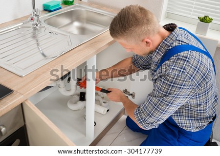 Male Plumber Fixing Sink Pipe With Adjustable Wrench In Kitchen - stock photo
