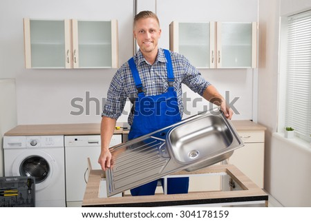 Male Plumber Fixing Stainless Steel Sink In Kitchen