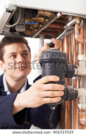 Male Plumber Working On Central Heating Boiler - stock photo