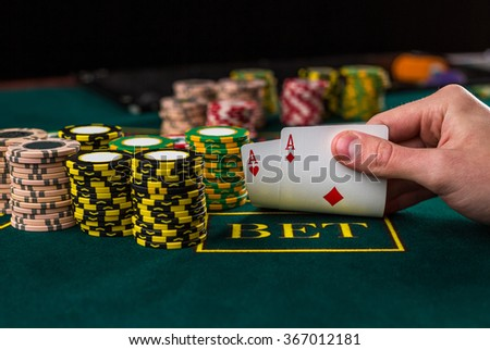 Male poker player lifting the corners of two cards aces  - stock photo