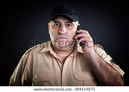 Male portrait, security guard talking on phone. Telecommunications.