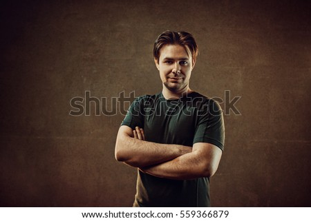 Male positive portrait. On dark stone wall background. Warm colors.