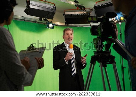 Male Presenter In Television Stdio With Crew In Foreground - stock photo
