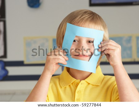 Male Primary School Cutting Out Paper Shapes In Craft Lesson - stock photo