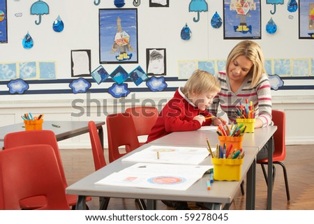 Male Primary School Pupil And Teacher Working At Desk In Classroom - stock photo