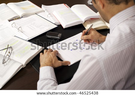 Male professional sitting at desk in office drawing a flow-chart and being busy studying books, rear view. - stock photo