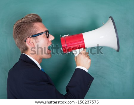 Male Professor Shouting Though Megaphone Against Chalkboard - stock photo