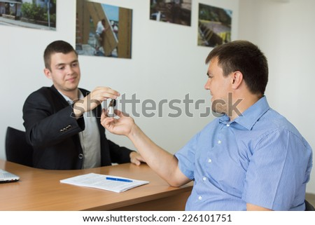 Male Property Agent Giving the House Key to Middle Age Male Client at the Office. - stock photo