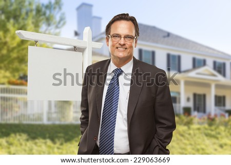 Male Real Estate Agent in Front of Blank Home For Sale Sign and House. - stock photo