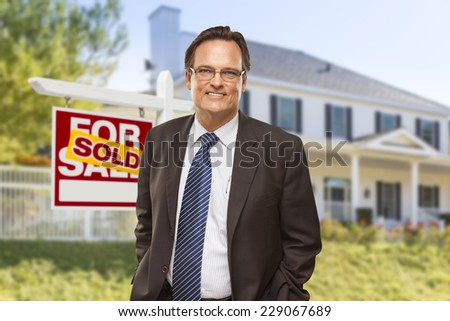 Male Real Estate Agent in Front of Sold Home For Sale Sign and House. - stock photo