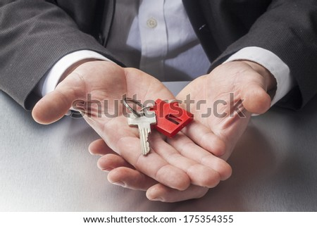 male realtor handing keys for property ownership - stock photo