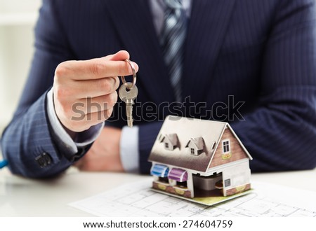 Male realtor selling house or apartment giving a key to client with building model at table. Shallow depth of field.    - stock photo