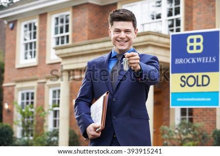 Male Realtor Standing Outside Residential Property Holding Keys - stock photo