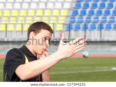 Male referee against the background of a football stadium - stock photo