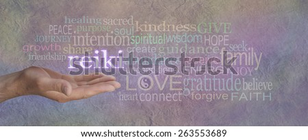 Male Reiki Healer with Healing Word Cloud - man's hand, open with the word 'REIKI' floating above, surrounded by a healing relevant word cloud on a grey lilac stone effect background wide banner - stock photo