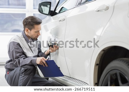 Male repair worker examining car paint with equipment in repair shop - stock photo