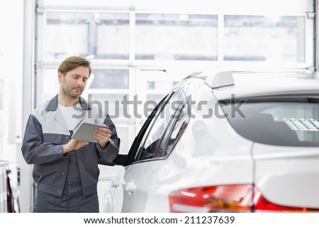 Male repair worker using tablet PC while standing by car in workshop - stock photo