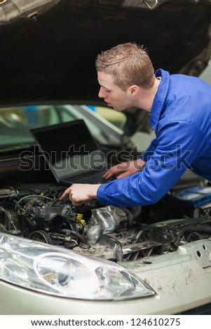 Male repairman with laptop checking car engine - stock photo