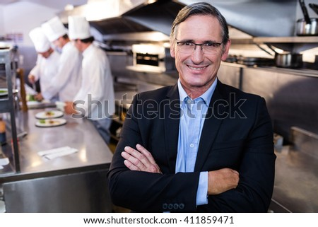 Male restaurant manager standing with arms crossed in commercial kitchen - stock photo