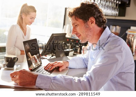 Male restaurant manager working on laptop - stock photo