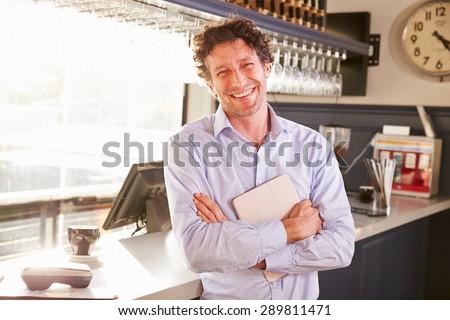 Male restaurant owner holding digital tablet, portrait - stock photo