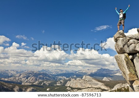 Male rock climber celebrates on the summit after a successful ascent.