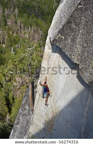 Male rock climber clings to a steep crack on the side of a granite cliff. - stock photo