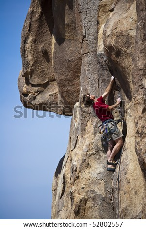 Male rock climber  clings to an overhang in Hidden Valley  Canyon on a sunny day. - stock photo
