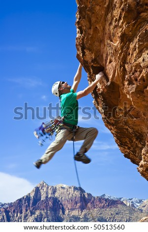 Male rock climber  clings to an overhang in Red Rock Canyon on a sunny day. - stock photo