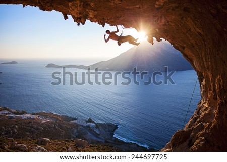 Male rock climber flexing his bicep while hanging on one arm at sunset. Climbing along roof in cave, Kalymnos, Greece. - stock photo