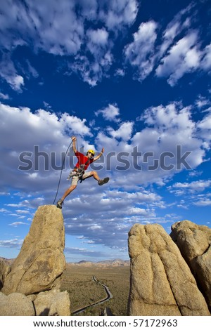 Male rock climber leaps across a gap on the summit of a pinnacle with a cloud filled sky behind him. - stock photo