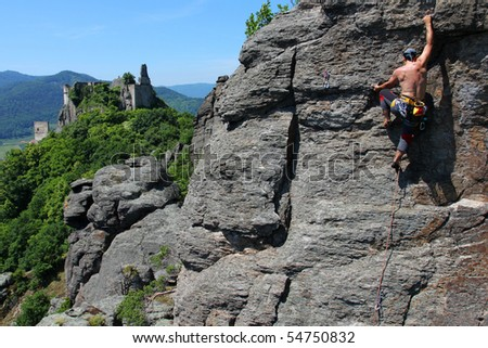 Male rock-climber  on a granite wall with magnificent view - stock photo