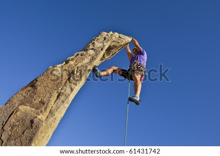 Male rock climber scrambles to the summit of a sheer pinnacle. - stock photo