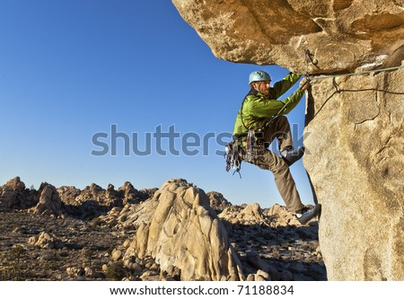 Male rock climber struggles for his next grip as he clings to a sheer cliff. - stock photo