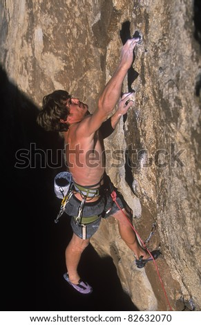 Male rock climber struggles up the edge of a challenging cliff. - stock photo
