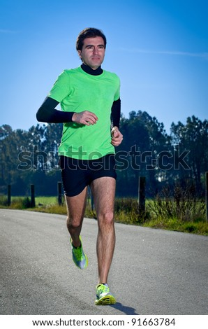 Male runner at sprinting speed training for marathon outdoors on c country landscape. - stock photo